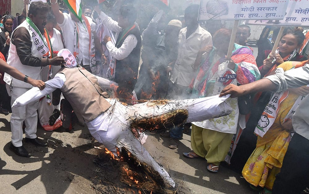 Congress workers burn an effigy of Prime Minister Narendra Modi during a protest at Malad in Mumbai on the first anniversary of the NDA Government.