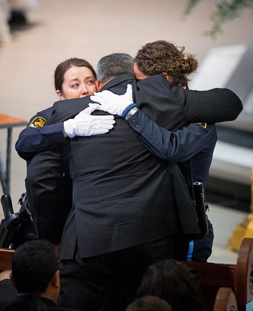 Two Omaha police officers embrace Hector Orozco, the husband of Kerrie Orozco, near the end of her funeral service at St. John's Catholic Church at Creighton University in Omaha, Neb. Orozco, 29, was shot and killed May 20, 2015 in Omaha.