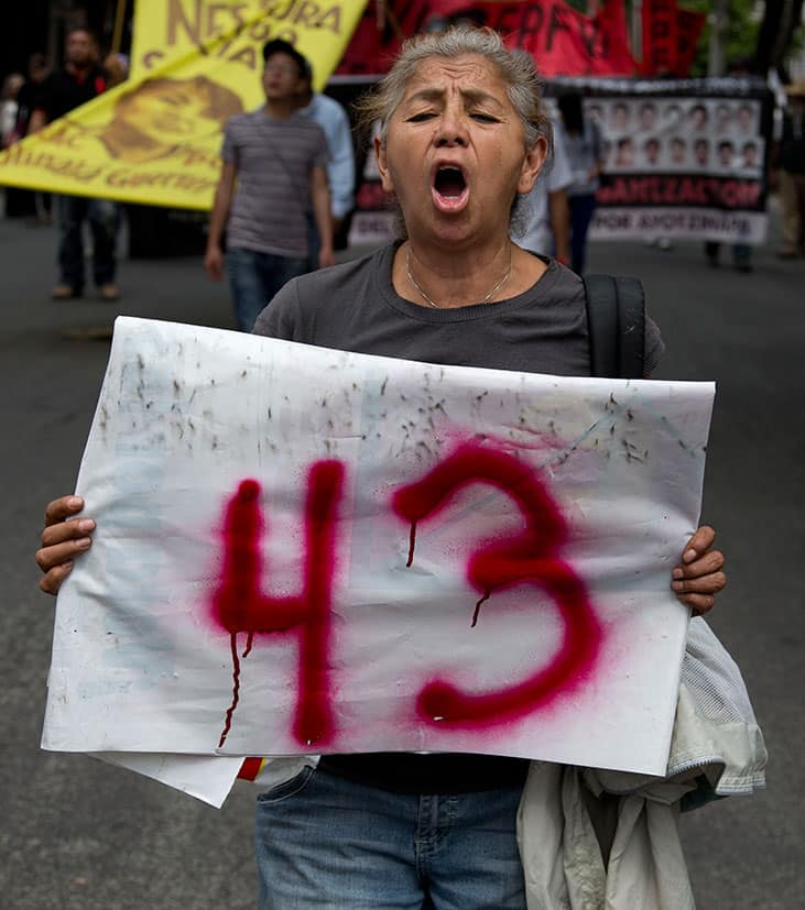 A woman holds a sign with the number 43 in reference to the missing students from a rural teachers college, during march marking the eigth month since their disappearance, in Mexico City.