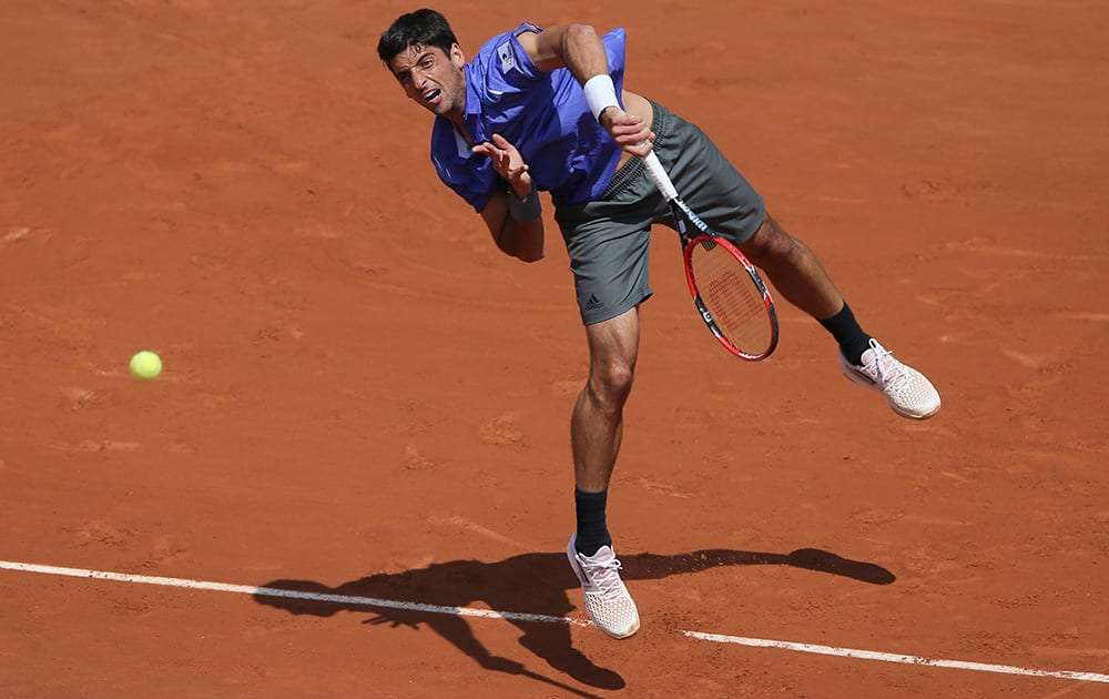 Brazil's Thomaz Bellucci serves in the second round match of the French Open tennis tournament against Japan's Kei Nishikori at the Roland Garros stadium, in Paris, France.