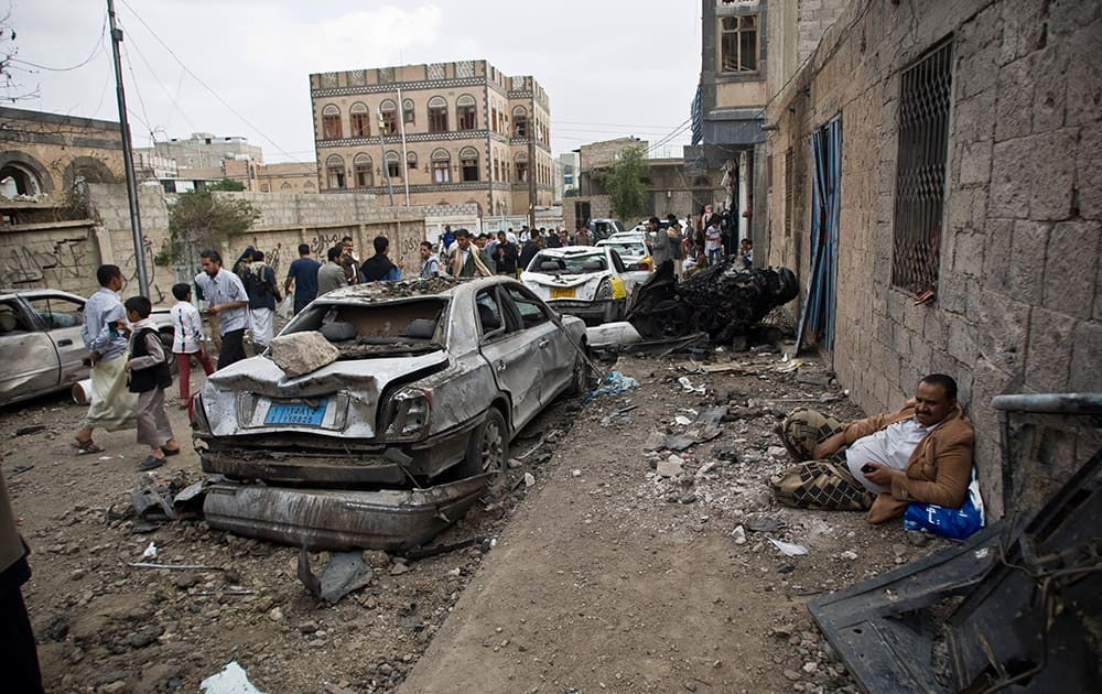 A man rests next to his car destroyed by Saudi-led airstrikes in Sanaa, Yemen.