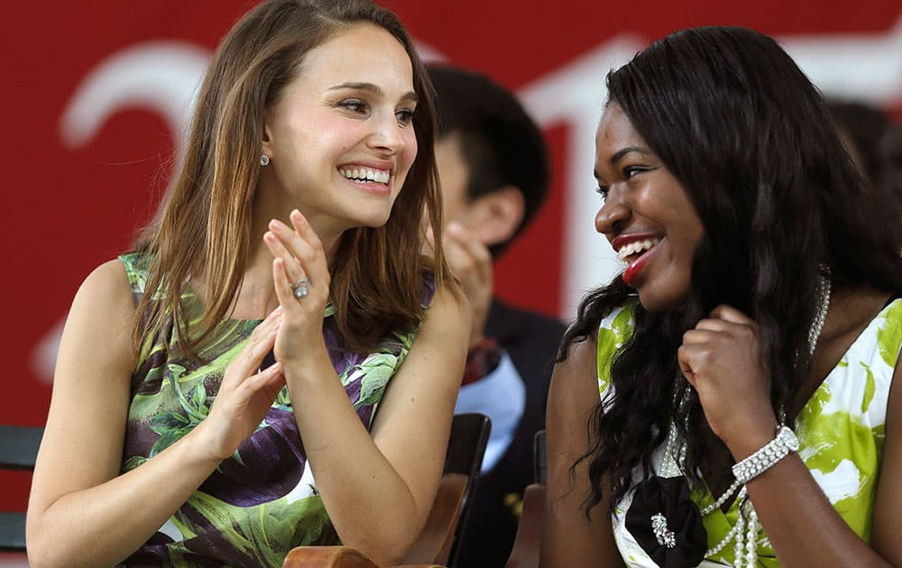 Actress Natalie Portman, left, speaks with graduating Harvard College student Chisom Okpala, right, on stage at Harvard College's Class Day, on the campus of Harvard University, in Cambridge, Mass. Portman, a 2003 Harvard graduate, was the 2015 Class Day speaker for Harvard College.