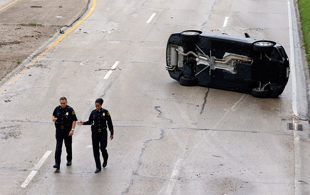 Dallas police officers walk away from an overturned vehicle on Northwest Highway close to Harry Hines Blvd. in Dallas. Several vehicles were stranded due to the heavy rains and flash flooding.