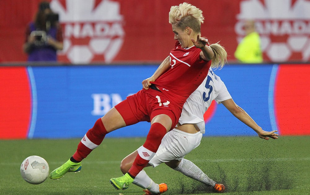 Canada's Sophie Schmidt battles for the ball with England's Steph Houghton during the second half of a women's international soccer friendly match in Hamilton, Ontario.