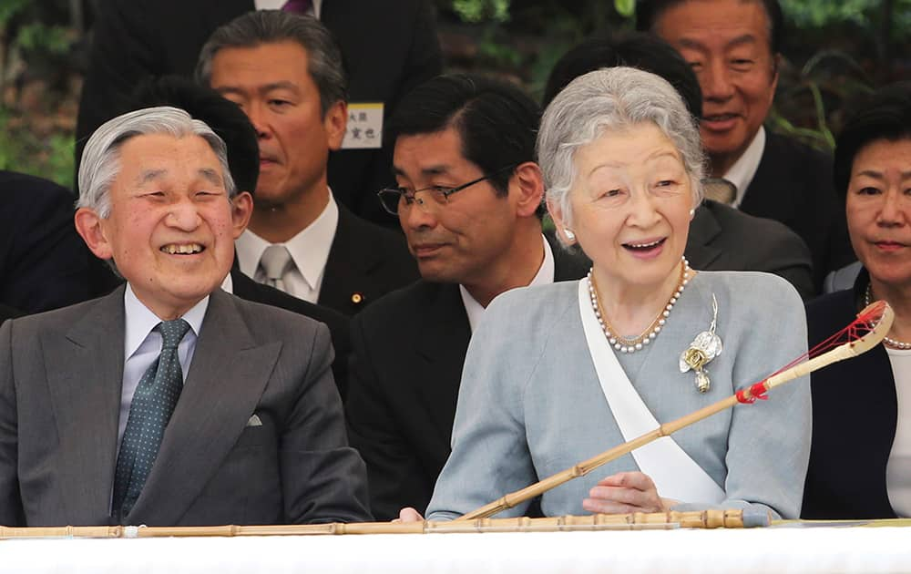 Japanese Emperor Akihito and Empress Michiko enjoy watching a demonstration of the Japanese traditional horsemanship 'dakyu,' the ancient Japanese lacrosse on horseback, while holding a 'kyujo,' a racket for dakyu, at the Imperial Palace in Tokyo.