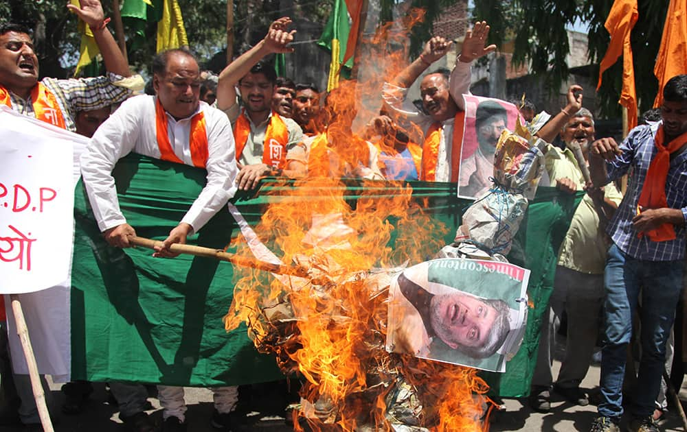 Activists of Hindu right-winged Shiv Sena burn an effigy of Kashmiri separatist leader Shabir Ahmad Shah along with a flag of Pakistan in Jammu.