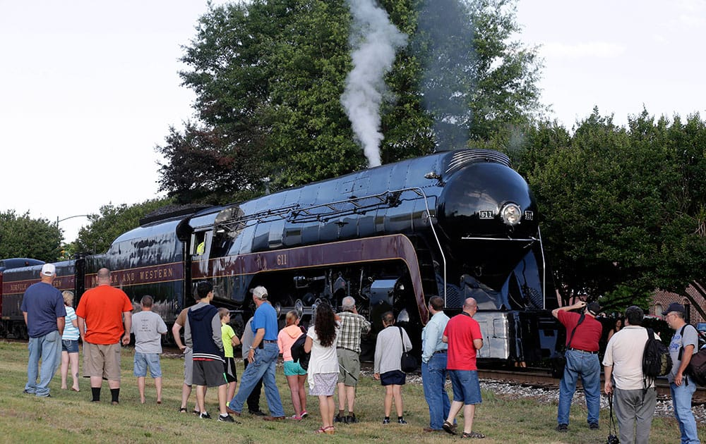 People take photos of the Norfolk & Western Class J No. 611 steam locomotive before it leaves the North Carolina Transportation Museum in Spencer, N.C.