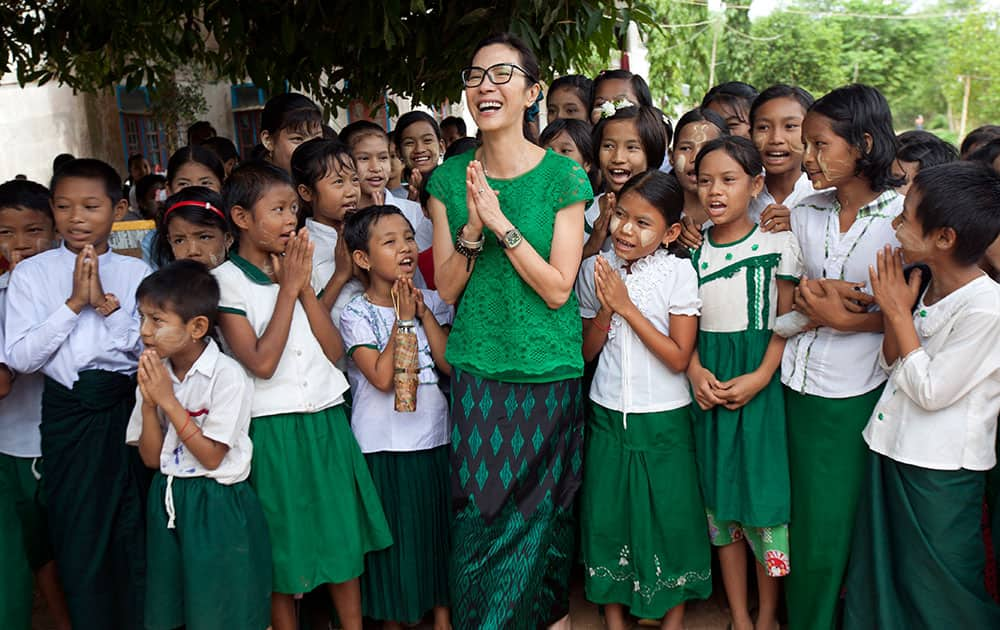 Malaysian actress Michelle Yeoh, center, global ambassador for the Make Roads Safe Campaign, laughs as she poses with orphans for a group photo during her visit to a monastic school in Kaw-Hmu in the outskirts of Yangon, Myanmar.