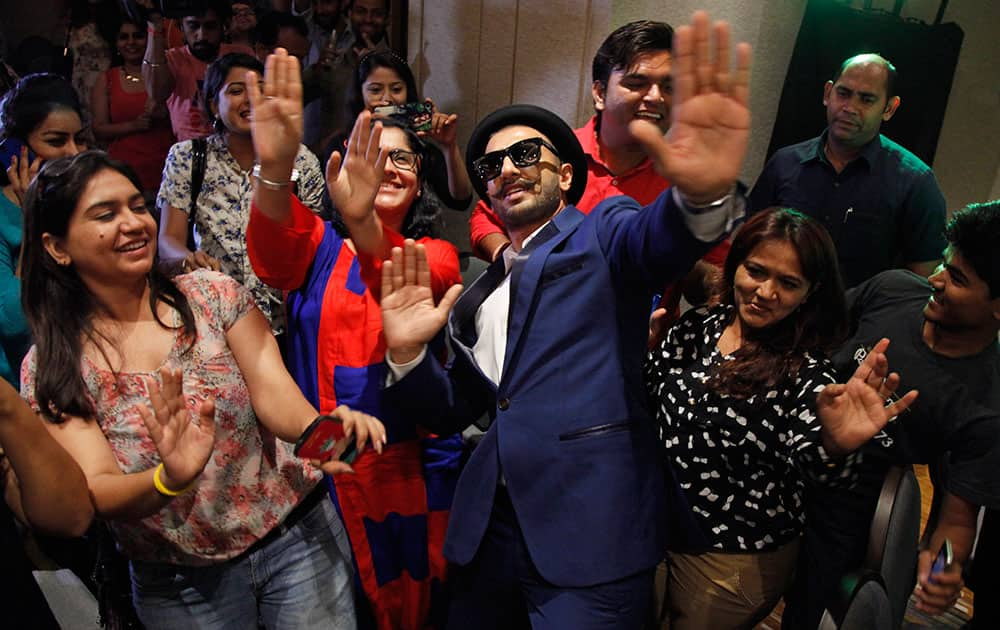 Bollywood actor Ranveer Singh, center, dances with members of the media during a press conference for his upcoming film