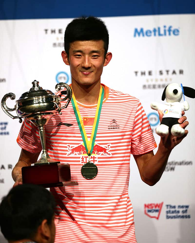 Chen Long of China smiles with his victory medal and trophy after winning his men's singles final against Victor Axelsen of Denmark at the Australian Badminton Open in Sydney.