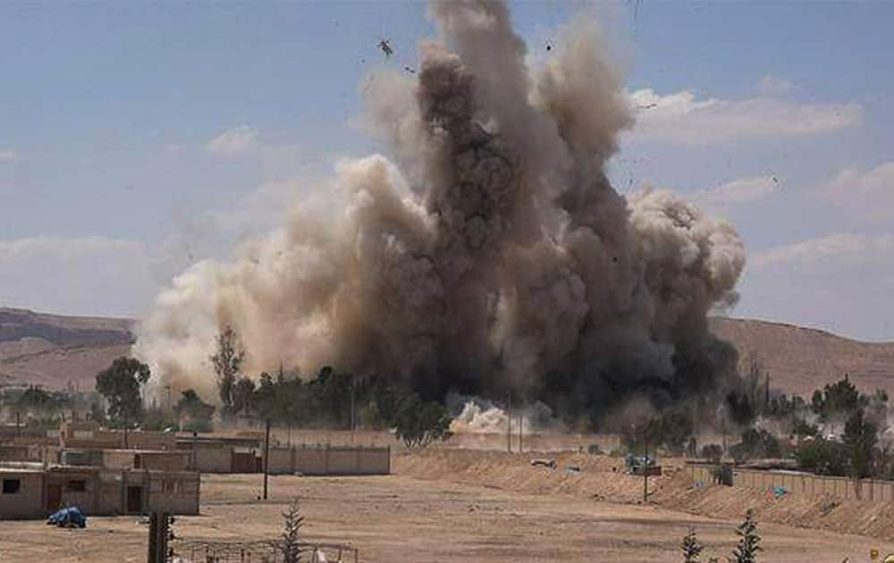 smoke rises at Tadmur prison after being blown up and destroyed by the Islamic State group at Palmyra Town, in Homs province, Syria.