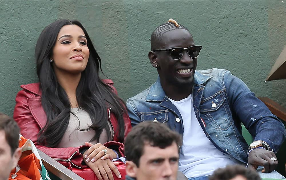 Liverpool French soccer player Mamadou Sakho and his wife Majda watch France's Jo-Wilfried Tsonga playing Tomas Berdych of the Czech Republic during their fourth round match of the French Open tennis tournament at the Roland Garros stadium.