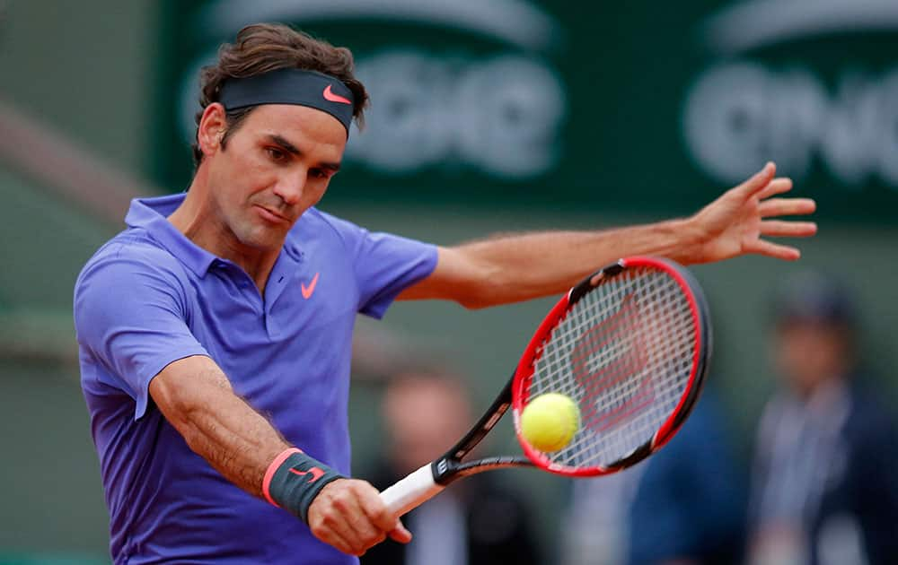 Switzerland's Roger Federer returns the ball to France's Gael Monfils during their fourth round match of the French Open tennis tournament at the Roland Garros stadium.