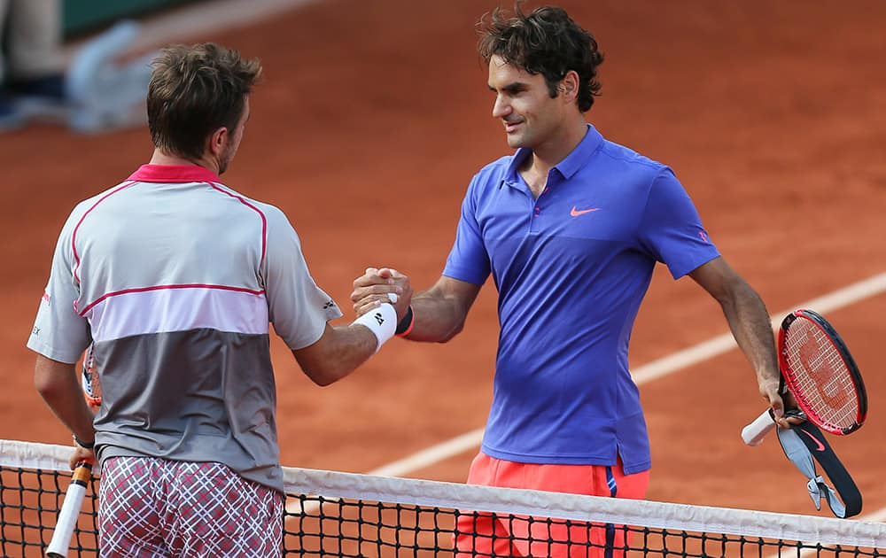 Switzerland's Stan Wawrinka shakes hands with compatriot Roger Federer, right, after winning the quarterfinal match of the French Open tennis tournament in three sets 6-4, 6-3, 7-6 (7-4), at the Roland Garros stadium, in Paris, France.