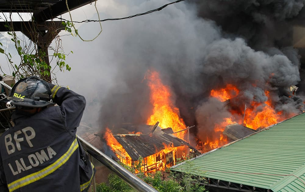 A fireman shields himself from burning houses which gutted a neighborhood of informal settlers in suburban Quezon city, northeast of Manila, Philippines.