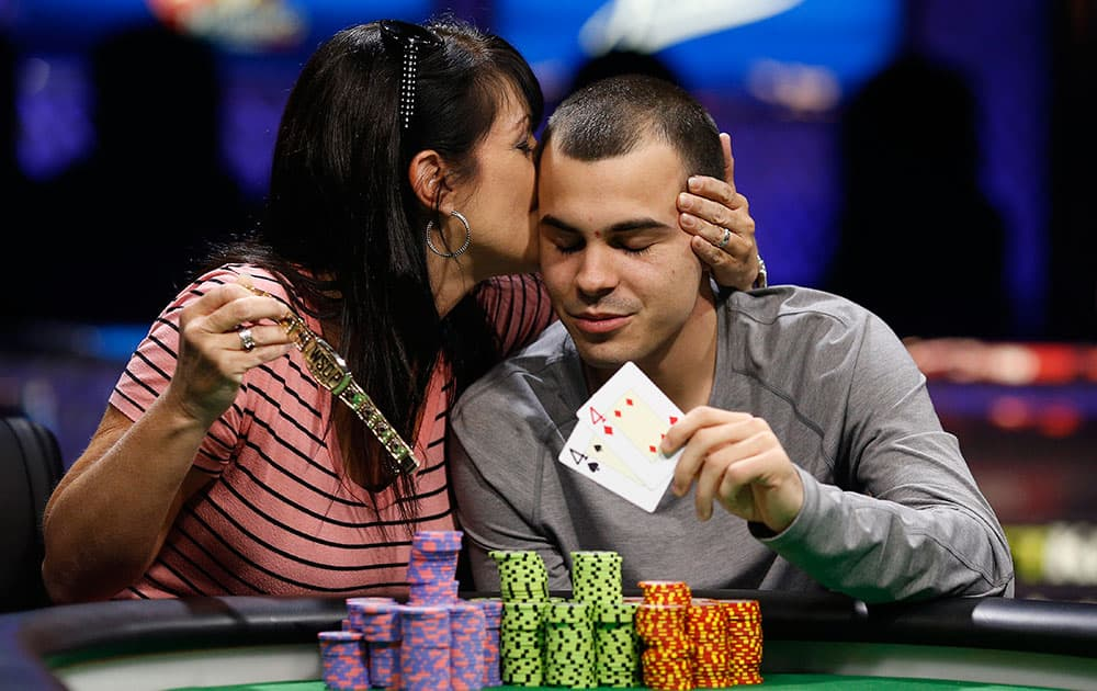 Lance Garcia gets a kiss from his mother, Kristen Scott, while posing for photographers after he won the World Series of Poker Colossus event, in Las Vegas.