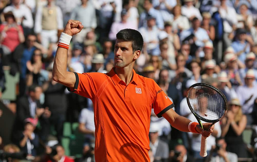 Serbia's Novak Djokovic celebrates winning the quarterfinal match of the French Open tennis tournament against Spain's Rafael Nadal in three sets, 7-5, 6-3, 6-1, at the Roland Garros stadium, in Paris, France.