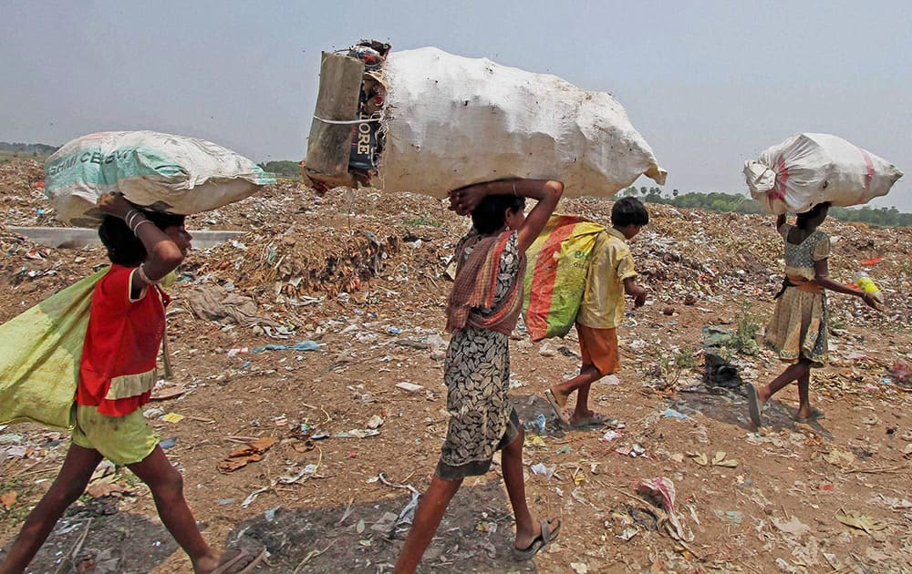 Rag pickers returning home after collecting recyclable items from an open garbage dump on the eve of World Environment Day at Sian in Birbhum district of West Bengal.