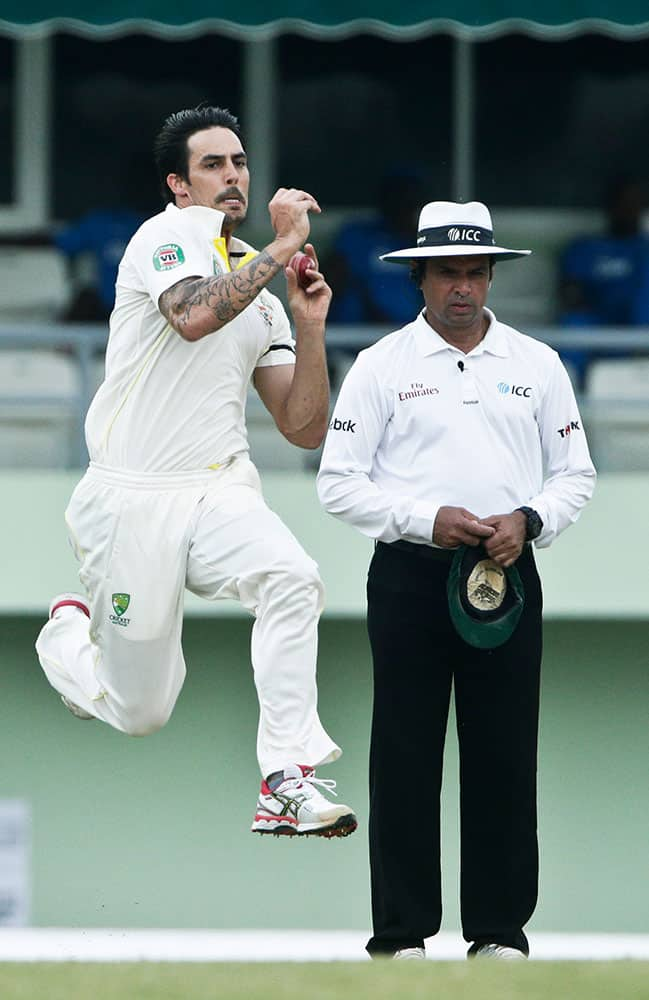Australia's bowler Mitchell Johnson, left, bowls past umpire Aleem Darl, right, of Pakistan, during the second inning on the day two of their first cricket Test match against West Indies in Roseau, Dominica.