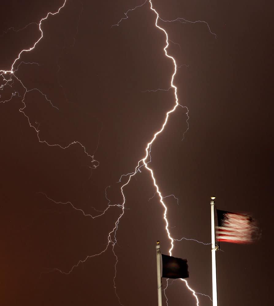 Lightning strikes behind flags at the Kansas Veterans' Cemetery, in WaKenney, Kan.