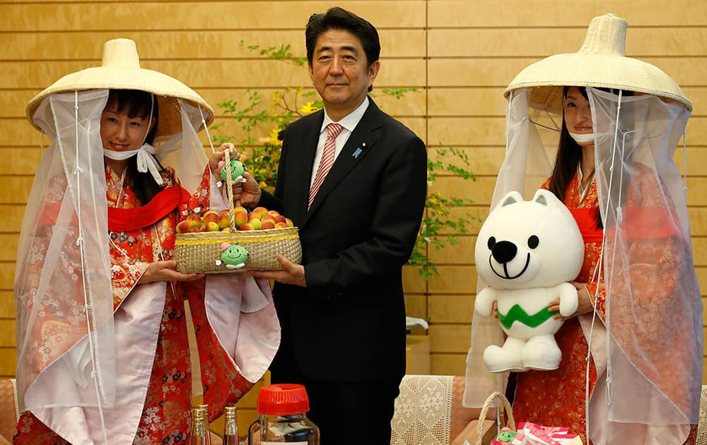 Japan's Prime Minister Shinzo Abe poses with Miss Plum Kozue Kimoto and Fuyuka Baba who are representing the Kishu Plum Organization as he is presented a basket of plums during their courtesy call at Abe's official residence in Tokyo.