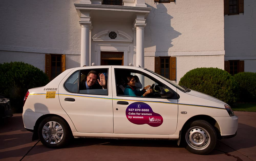Netherlands' Prime Minister Mark Rutte waves to the media as he takes a ride in a taxi driven by Shanti Devi Sharma, a woman driver for taxis driven by women and mainly for women riders in New Delhi.