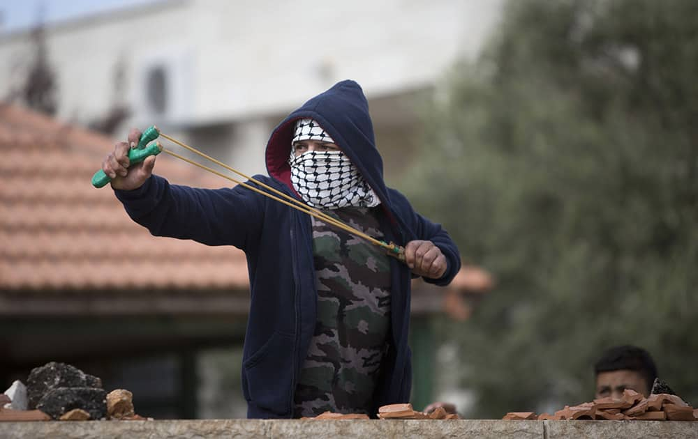A Palestinian boy uses a catapult to hurl rocks at Israeli soldiers, during an occasional protest against the nearby Jewish settlement Ofra, in the village of Silwad near the West Bank city of Ramallah.