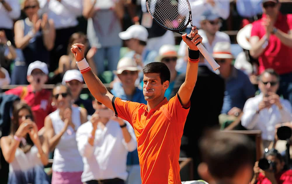 Serbia's Novak Djokovic raises his arms after defeating Britain's Andy Murray during their semifinal match of the French Open tennis tournament at the Roland Garros stadium in Paris.