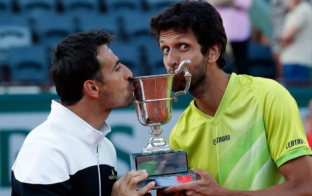 Croatia's Ivan Dodig, left, and Brazil's Marcelo Melo bite the cup after defeating Bob and Mike Bryan of the U.S. in their men's doubles final match of the French Open tennis tournament at the Roland Garros stadium.