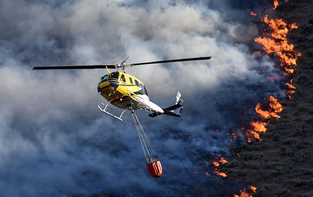 Emergency responders dump water onto a wildfire, near Celebration Park south of Melba, Idaho.