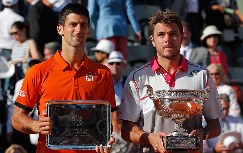 Switzerlands Stan Wawrinka, right, holds the trophy after winning the mens final of the French Open tennis tournament in four sets, 4-6, 6-4, 6-3, 6-4, against Serbias Novak Djokovic, left, at the Roland Garros stadium, in Paris.