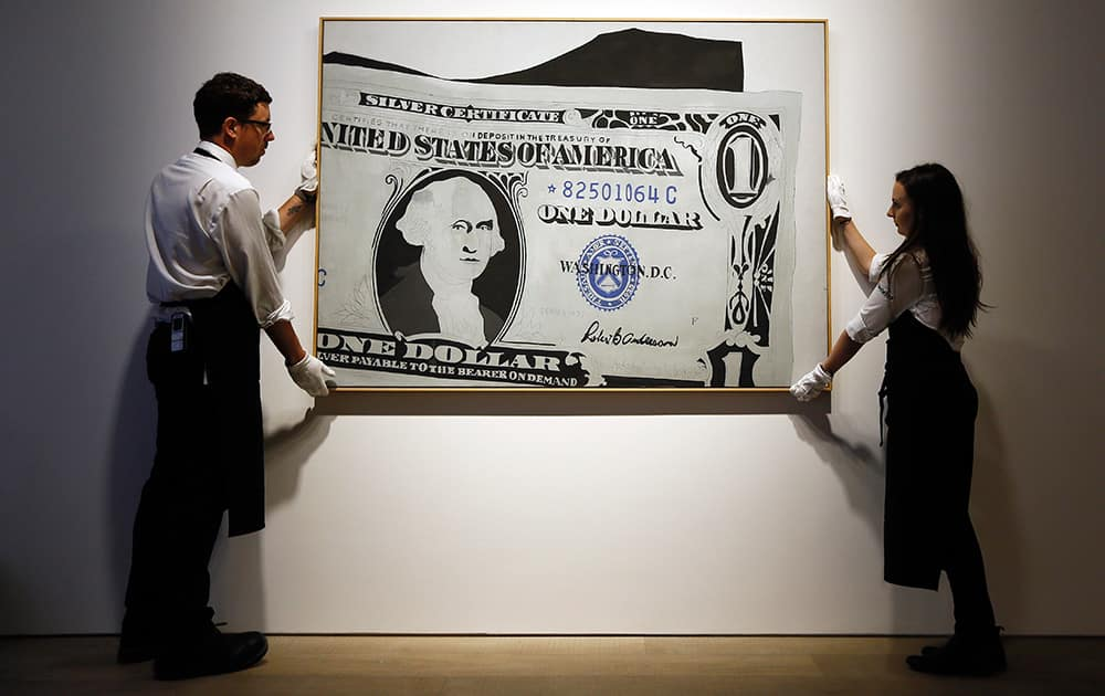 Two employees stands with an artwork by Andy Warhol called 'Silver Certificate' estimated at £13-£18 million (19.8-27.4 million US dollars) at Sotheby's auction house in London.