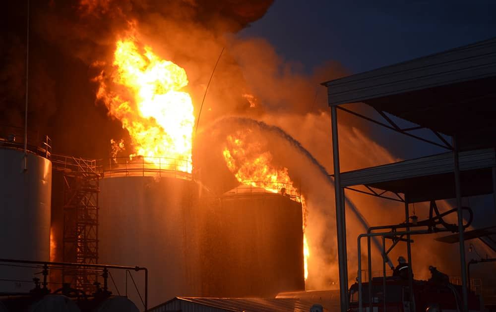Ukrainian firemen distinguish fire at a fuel depot near Hlevaha, Kiev region, Ukraine. At least one killed and a number of firemen were injured on Tuesday as they fought to control a blazing fuel depot outside Ukraine's capital Kiev.