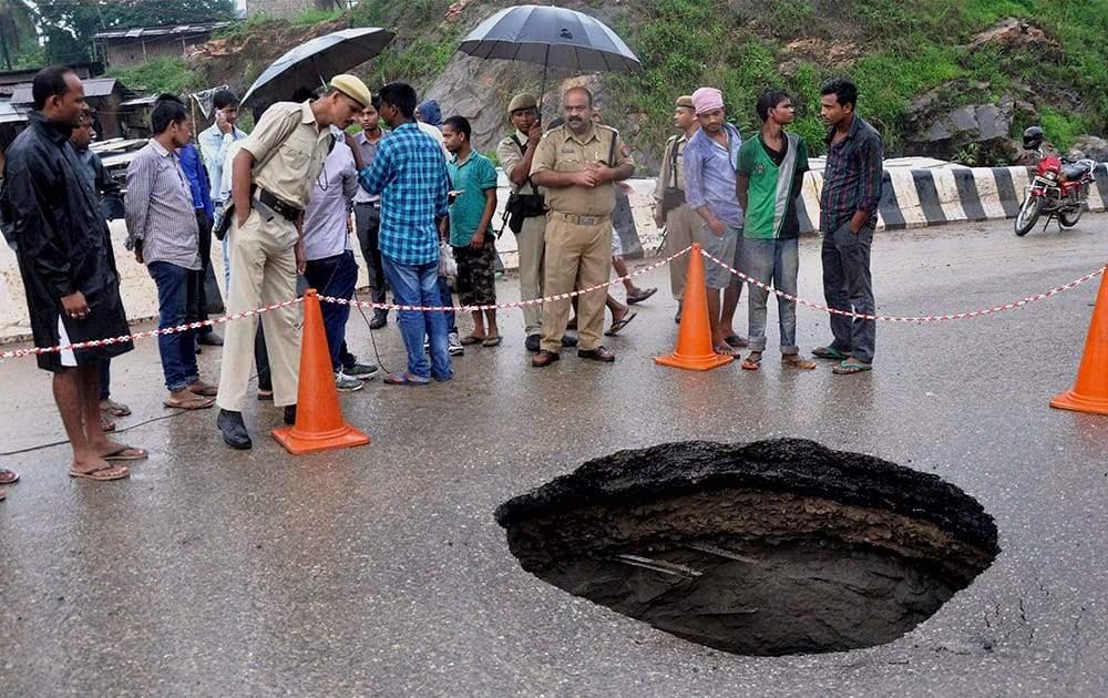 Security personnel and local people standing near a huge pothole occurred on the National Highway 37, at 8th Mile in Guwahati