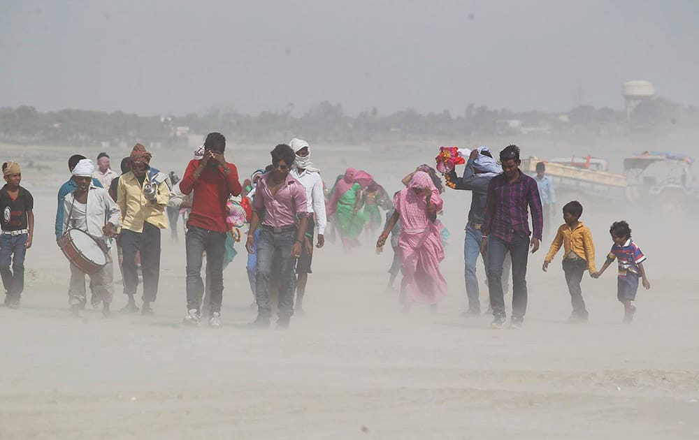 People cover themselves as they walk on the banks of the river Ganges during a dust storm in Allahabad.