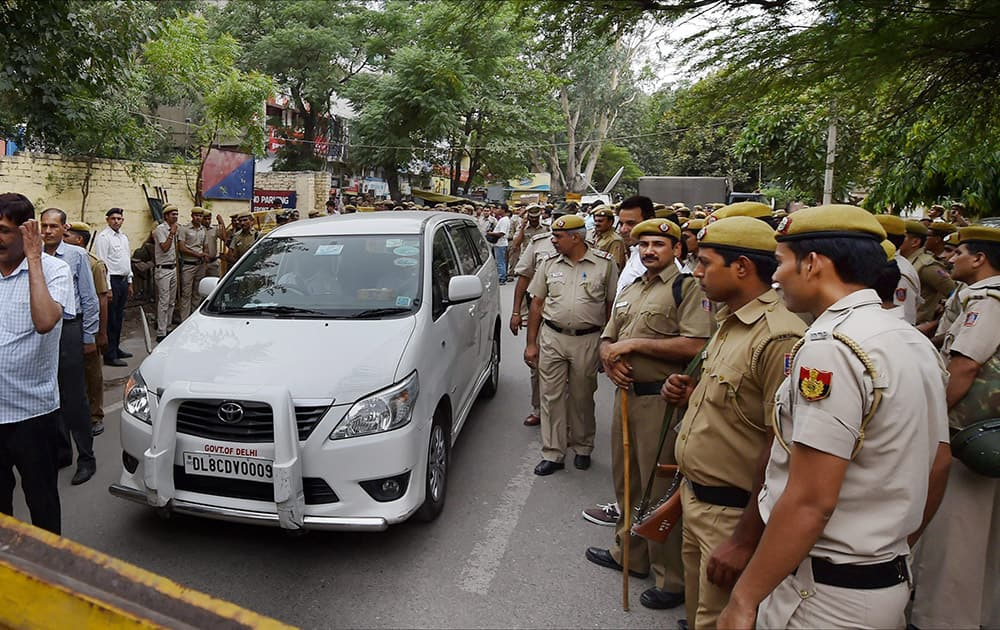 Policemen standing near Delhi Law Minister Jintender Singh Tomars vehicle at the ATS Office Vasant Vihar where he was being questioned following his arrest in alleged fake degree case in New Delhi.