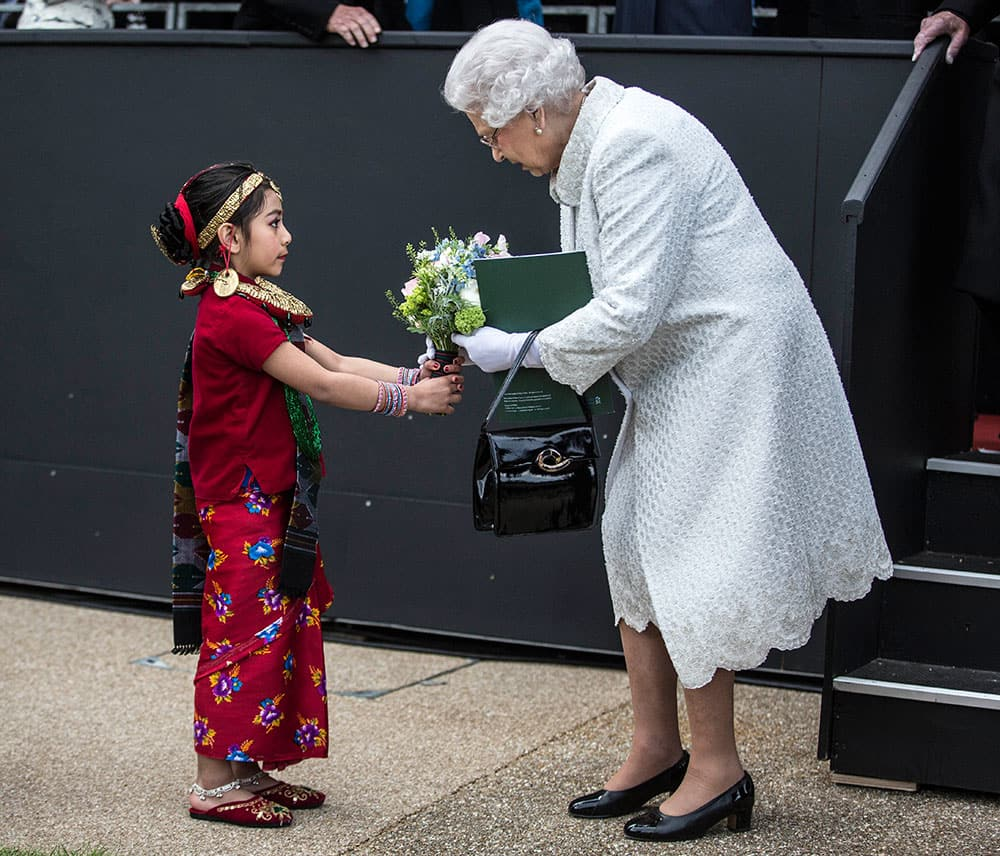 Britain's Queen Elizabeth II receives a bouquet of flowers from Swechya Joshi, the daughter of a serving Gurkha after a pageant to celebrate 200 years of Gurkha service to the British Crown in London.
