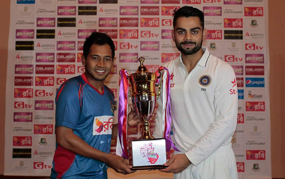 India's test match captain Virat Kohli, right, and Bangladesh's test match captain Mushfiqur Rahim pose with the trophy on the eve of the only test match of their series in Dhaka, Bangladesh.