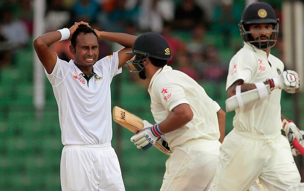 Bangladesh's Mohammad Shahid, left, reacts as India's Murali Vijay, center, and Shikhar Dhawan run between wickets during the test cricket match between them in Fatullah, Bangladesh.