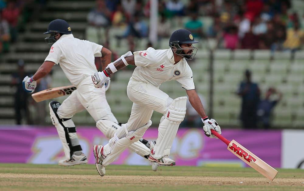 Murali Vijay and Shikhar Dhawan run between wickets during the first day of their test cricket match against Bangladesh in Fatullah, Bangladesh.