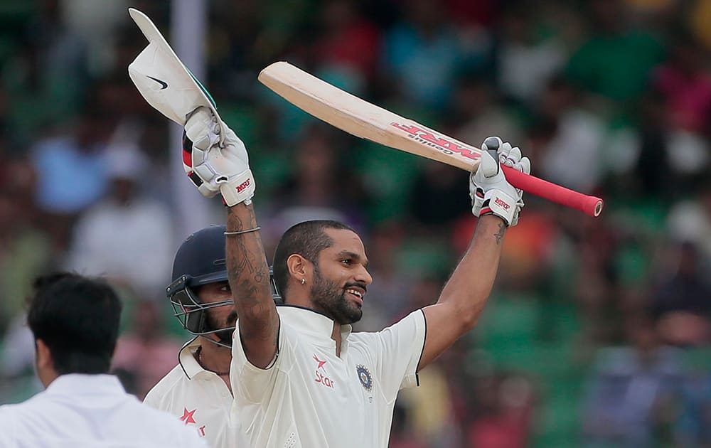 Shikhar Dhawan, acknowledges the crowd after scoring a hundred runs during the first day of their test cricket match against Bangladesh in Fatullah, Bangladesh.
