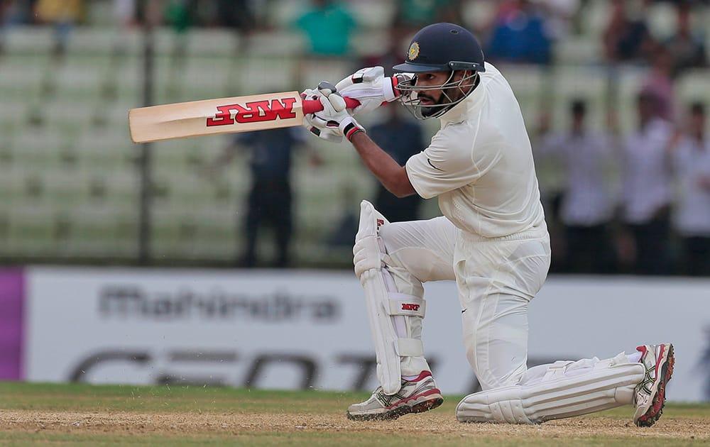 Shikhar Dhawan, plays a shot during the first day of their test cricket match against Bangladesh in Fatullah, Bangladesh.