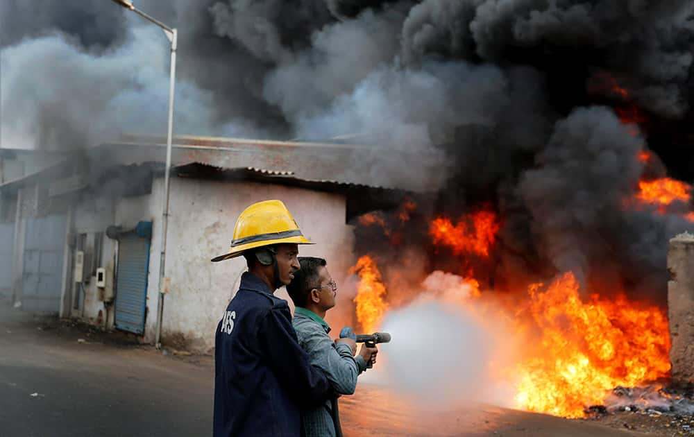 Firefighters extinguishing fire in a market selling used oil barrels in Ahmedabad.