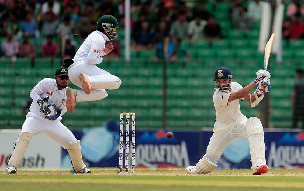 Ajinkya Rahane plays a shot as Bangladesh's Mominul Haque jumps during the third day test cricket match against Bangladesh in Fatullah, Bangladesh.