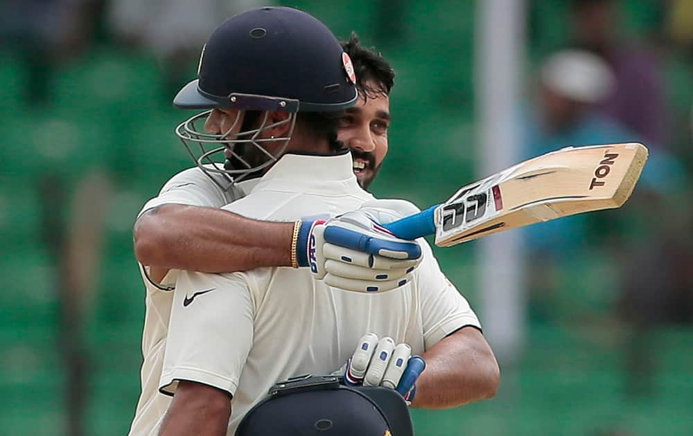 Murali Vijay hugs his teammate Shikhar Dhawan after scoring a century during the third day test cricket match against Bangladesh in Fatullah, Bangladesh.