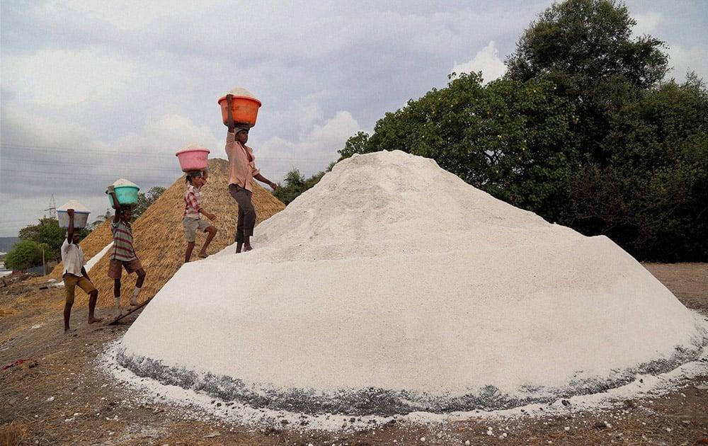 Labourers collecting salt in the salt pans before the monsoon rain near Airoli creek in Mumbai.