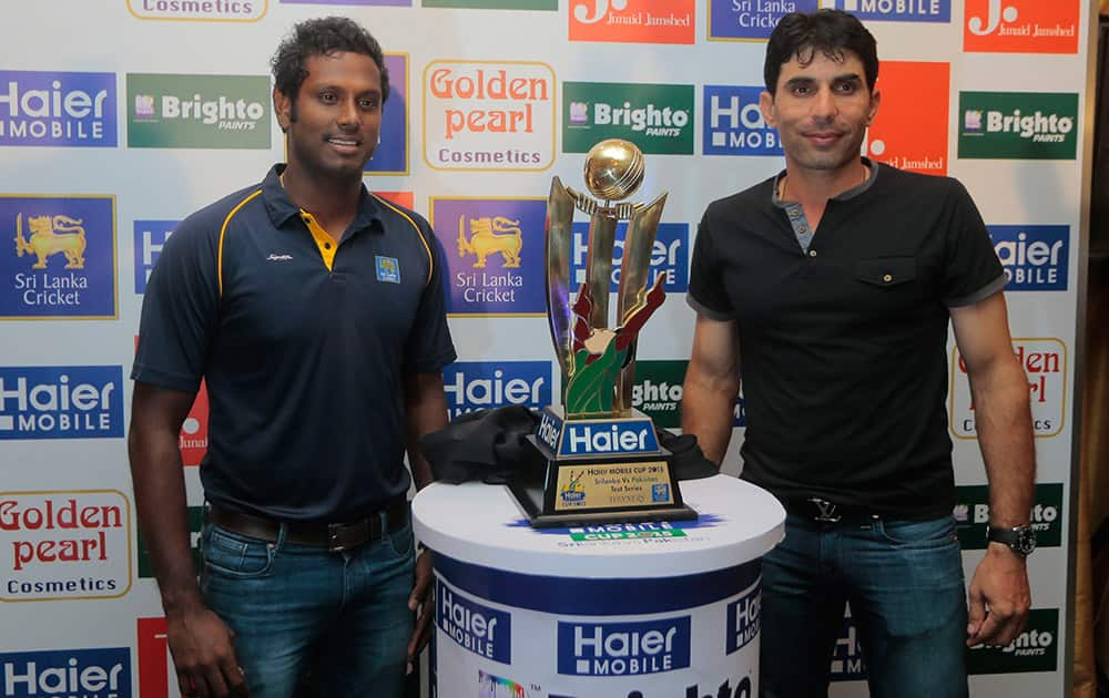 Pakistani cricket captain Misbah-ul- Haq, right, and Sri Lankan cricket captain Angelo Mathews pose for photographs with the test series trophy in Colombo, Sri Lanka.