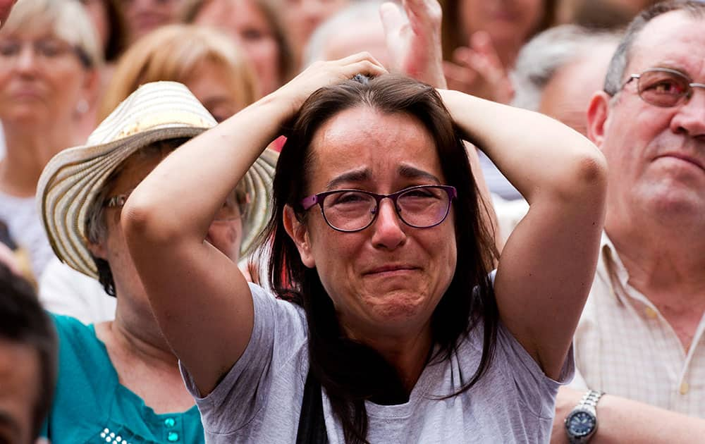 People react in front of the city town building to support the leader of leftist coalition Barcelona Together, Ada Colau, after been elected as Barcelona's new mayor in Barcelona, Spain.