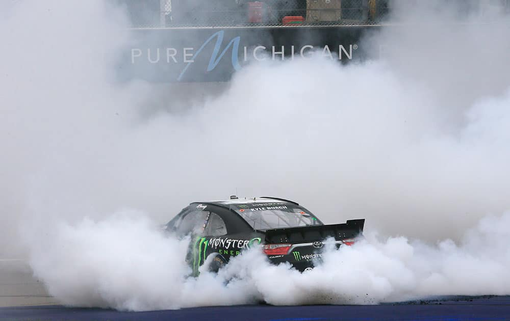 Kyle Busch burns out at the finish line after winning the NASCAR Xfinity series auto race at Michigan International Speedway, in Brooklyn, Mich.