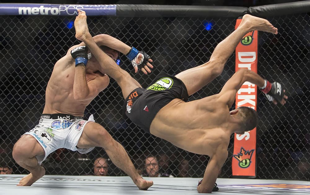 Charles Rosa, left, of the United States battles against Mexico´s Yair Rodriguez during a men's Featherweight UFC 188 mixed martial arts bout in Mexico City.